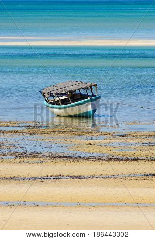 Fishing boat near cost of Mozambique with low tide