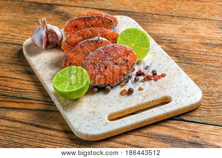 Fresh fish. Salmon. Raw salmon steak with sea salt, pepper and herbs. Food background.