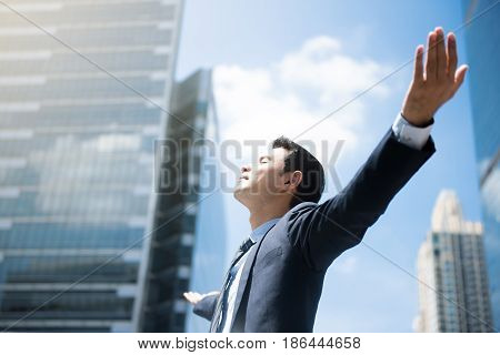 Happy businessman raising his arms open palms with face looking up - empower success and freedom concepts
