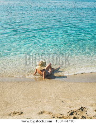 Beautiful slim senior woman tourist in bikini and hat lying on sand enjoying clear sea waters at Meditteranean resort of Turkey in Alanya, Kleopatra beach