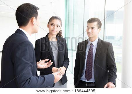 Business people talking in office building hallway
