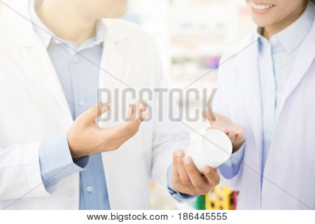 Pharmacist holding medicine bottle and discussing in pharmacy