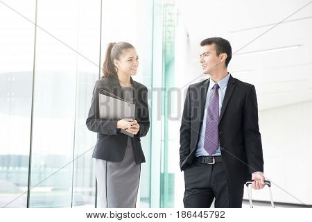 Businessman walking and pulling luggage handle while talking with a businesswoman in building hallway