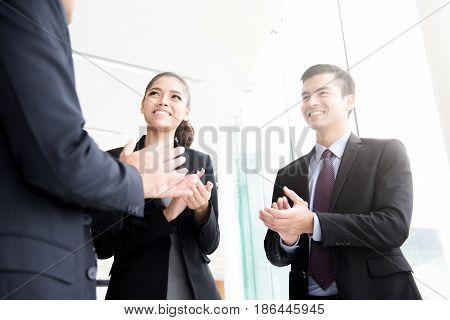 Business people clapping their hands at building corridor - praising congratulation and appreciation concepts