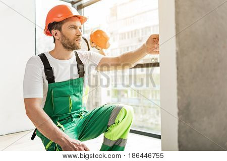 Concentrated builder is squatting near wall and rutting hand on it. He wearing work clothes. His colleague using building level