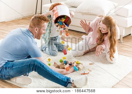 parents and little son playing with cubes at home family fun at home concept
