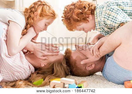 Side View Of Children Lying On Parents With Obscured Eyes, Big Family Portrait Concept