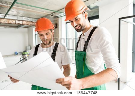 Builders are holding apartment plan and looking at it with attention. They standing in big unready room