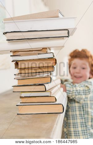 smiling little boy looking at pile of book focus on foreground