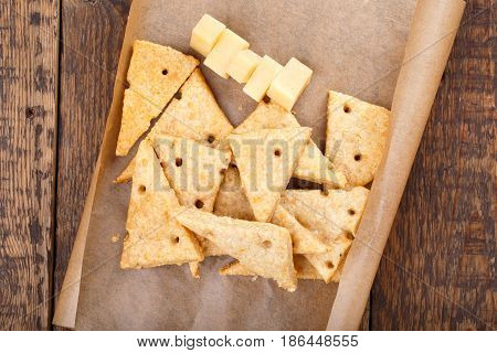 Homemade cheesy crackers shaped as slices of cheese. Perfect crispy snack. Top view.