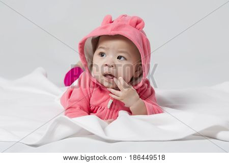 Cute Asian baby girl sucking finger on white background.