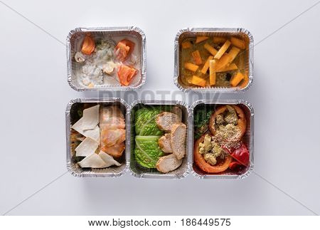 Healthy food delivery. Take away of natural fitness dishes for diet. Daily meals in foil boxes on white background