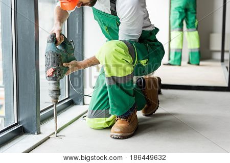 Busy builder using drill. He squatting near instrument. Coworker standing nearby wall