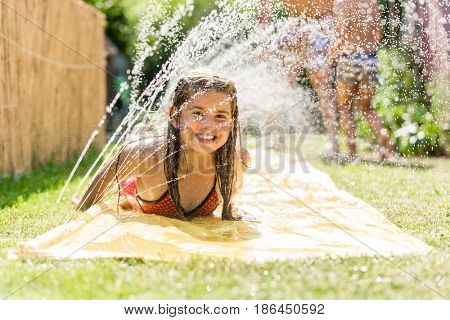 Water fun in garden - girl cooling down with water sprinkler on garden slide