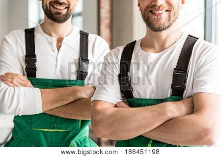 Cheerful repairmen are folding hands and standing with bright smiles in apartment. Focus on work clothes