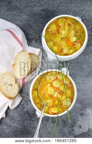 Vegetable crab sticks soup in two tureen and baguette. Top view