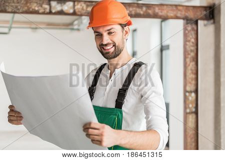 Busy builder is holding drafts and looking at with smile. He wearing work clothes. Portrait