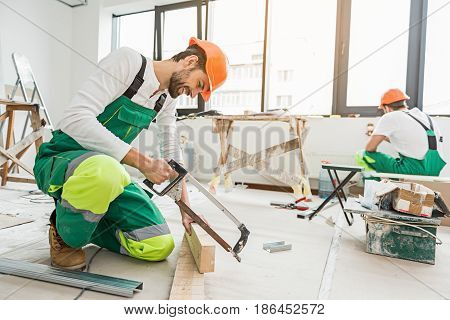 Busy repairmen are doing their job with help of different tools. They wearing work clothes
