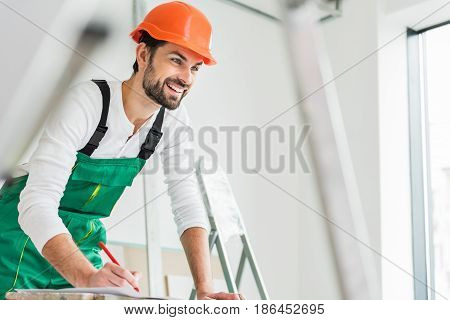 Happy constructor is inclining on table and holding pen. Man looking ahead with smile. Portrait