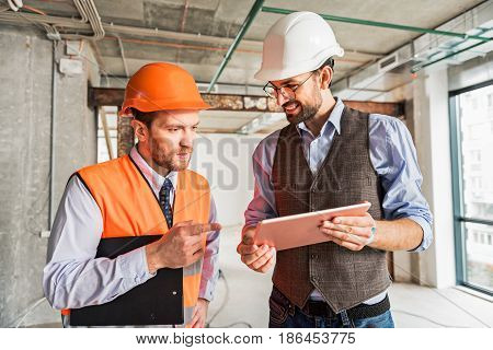 Happy smiling builder is holding tablet and show information to colleague, who keeping folder. They discussing certain case
