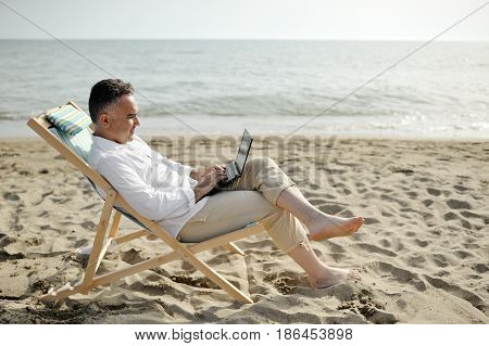 Man with laptop working on the beach sitting on a deckchair - freelance work concept