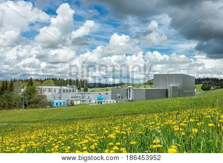 Factory in a rural scenic landscape on a flower meadow and nice sky. E cologically friendly cheese and milk dairy in Bavaria, Germany. Clean industry concept.