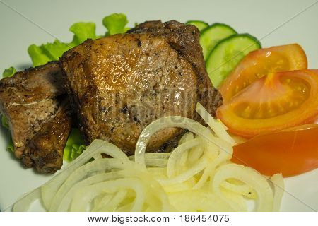Juicy grilled meat on a white plate with onions, cucumbers and tomatoes and a salad. close-up.