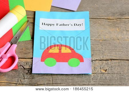 Happy Father's day card. Colored paper sheets, scissors, glue on vintage wooden background. Father's day gift children can make for dad. Children paper greeting card crafts. Closeup