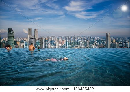 Asian girl swim in swimming pool on the roof top of hotel in Singapore city Singapore and summer concept