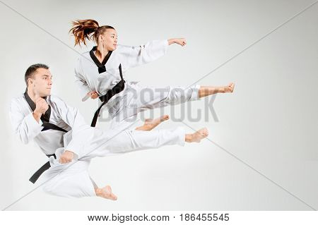 The karate girl and man in white kimono and black belt training karate over gray background and jumping