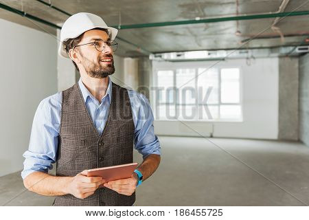 Merry builder is holing gadget and looking up with light smile. He standing in wide room. portrait