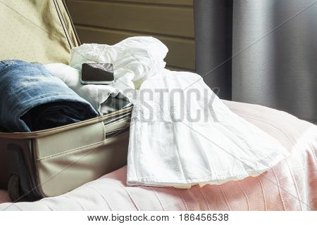 Open wooden door and view to the bedroom. Open suitcase with female clothes on the bed.