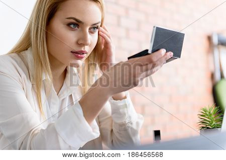 Natural beauty. Portrait of attractive woman looking at mirror while sitting on office chair. She checking her makeup