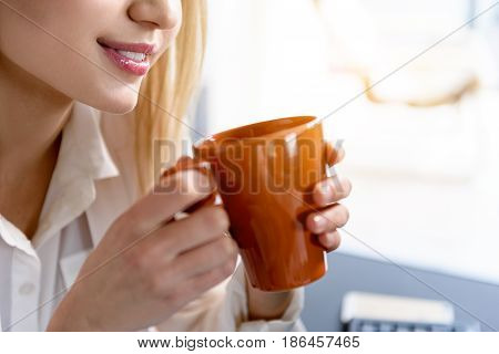 Coffee time. Young woman sitting in office with mug of drink. Focus on her hands with orange cup. Close up