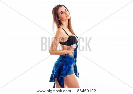 Adorable brunette lady with big natural breasts take off a shirt and looking at the camera isolated on white background