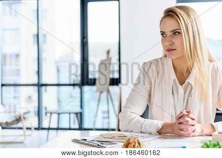 Let me think. Successful charming woman sitting at table in office and looking aside thoughtfully. Copy space in left side
