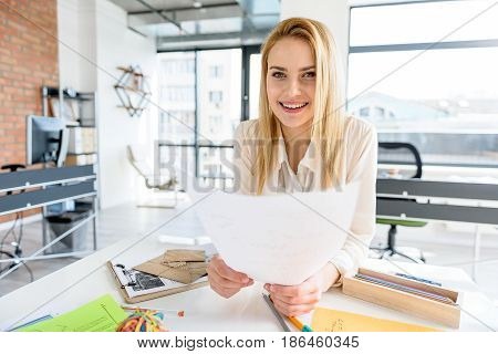 Joyful mood. Mysterious elegant woman with paper sheet looking at camera with joy. She is sitting in open-space office