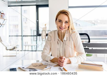 Perfect look. Portrait of attractive female posing with happiness. She is sitting at table while looking at camera charmingly