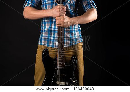 Music and art. The guitarist holds the electric guitar with his hands on a black isolated background. Playing guitar