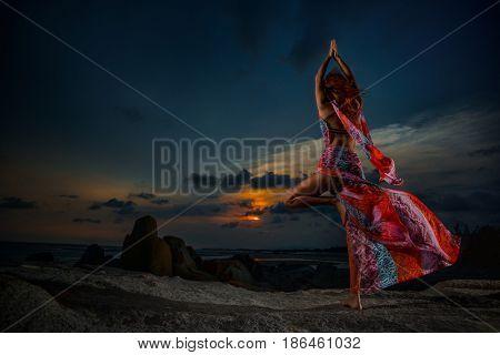 05 May 2015, Muine, VietNam, Young woman doing yoga Sun salutation Surya Namaskar, Tree Pose, Vrksasana on tropical beach at sunset