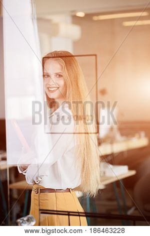 A Woman In An Office In Business Clothes: A Skirt And A White Blouse. Color Sample Book In Arms. Rea