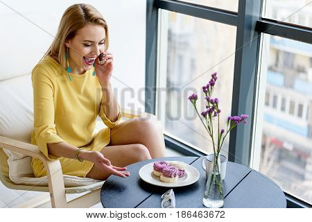 Glad to hear you. Attractive charming woman smiling and sitting at the table while having conversation on mobile phone. She gesturing positively