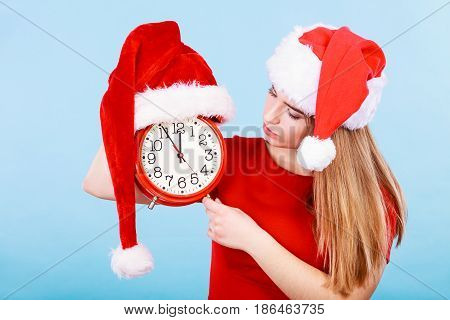Xmas seasonal clothing christmas time concept. Happy woman wearing Santa Claus helper costume holding big red clock waiting for celebration