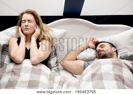 Snoring man in bed with wife