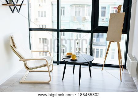 Comfort and pleasure. Round black wooden table with white chair and easel in conner. Cozy resting room against window