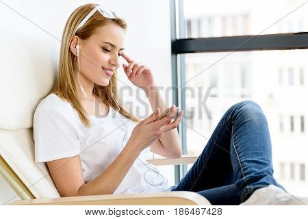 Feeling pleasure. Charming girl resting in chair while listening favorite song on gadget. She sitting against window and smiling