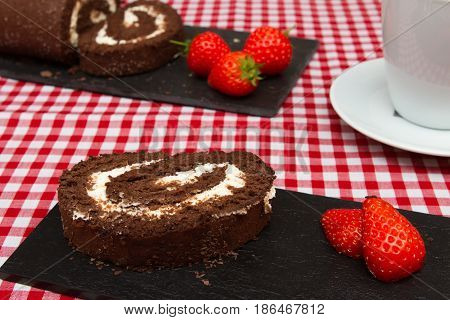 Chocolate swiss roll A chocolate swiss roll decorated with fresh strawberries