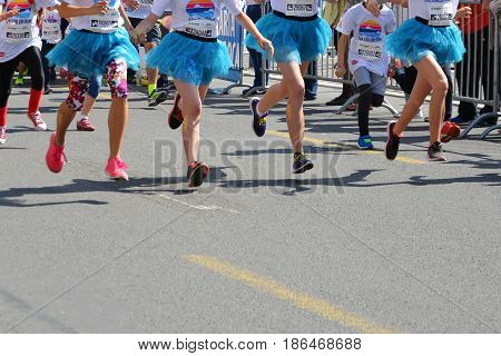 CLUJ-NAPOCA ROMANIA - May 14 2017: Color Run runners legs in the air as they start the run. Happy young girls with temporary tattoos on their legs wear blue tutus.