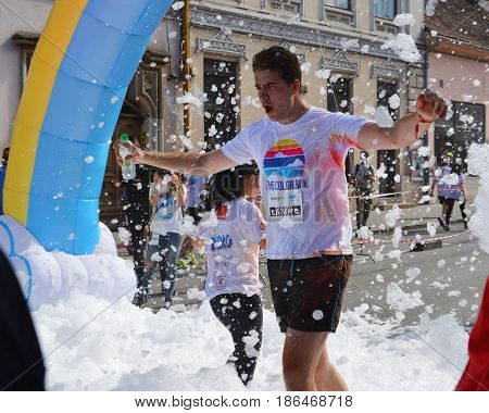 CLUJ-NAPOCA ROMANIA - May 14 2017: Young man enjoys the white foam bath at Color Run. White foam is floating in the air.