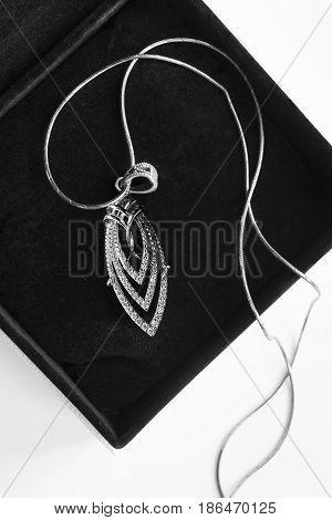 Elegant silver pendant with diamonds in black jewel box closeup